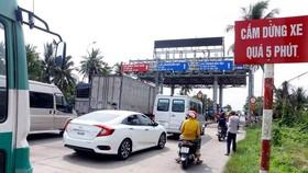 Các phương tiện dừng xe tại trạm BOT T1 để phản ứng việc trạm chưa thực hiện giảm giá theo quy định. (Ảnh: Thanh Liêm/TTXVN)