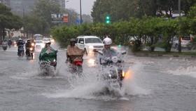 Các phương tiện lưu thông trong tình trạng ngập nước mỗi khi mưa lớn tại đường Nguyễn Hữu Cảnh, quận Bình Thạnh. (Ảnh: Xuân Dự/TTXVN)