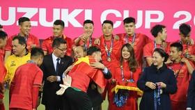 Thủ tướng Nguyễn Xuân Phúc chúc mừng từng thành viên của đội tuyển Việt Nam trên bục trao Cúp vô địch. Ảnh: DŨNG PHƯƠNG