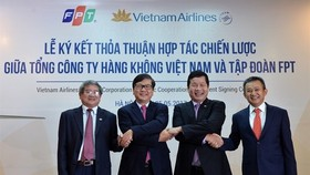 Representatives of Vietnam Airlines and FPT Corporation shake hands after signing strategic co-operation agreement in Hanoi. (Photo: VNA)