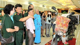 Painter Dang Ai Viet (Blue Ao Dai) presents to visitors her motorbike that she rode it to various parts of the country. (Photo: Sggp)