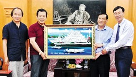 Representative of the SGGP Newspaper offers a painting as a gift to the CWA. (Photo: Sggp)