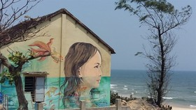 A portrait of a girl is painted on the wall of a house in Tam Thanh village in Quang Nam (Photo: VNA)