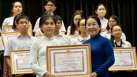 Vice Secretary of HCMC Party Committee Vo Thi Dung offers certificates of merit to students. (Photo: Sggp)