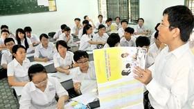 Giáo viên hướng dẫn học sinh ghi hồ sơ xét tuyển vào lớp 10. Ảnh: MAI HẢI
