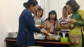 Nghệ nhân  Trương Thị Chiều (góc trái) đang giới thiệu các loại bánh tới khách mời trưa 5-3