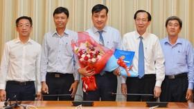 Phó Chủ tịch thường trực UBND TP Lê Thanh Liêm (thứ 2 từ trái sang) trao quyết định cho ông Lê Hòa Bình (giữa). ẢNh: VIỆT DŨNG