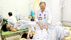 A doctor forgets to wear mask and glove when examining patients (Photo: SGGP)