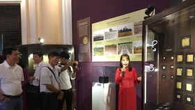 "Visitors listen to discussions about Oc Eo jewelry at the exhibition ""Bau vat Vuong quoc co - Nghe thuat kim hoan va trang suc Oc Eo"" (Treasures of Ancient Kingdom – Oc Eo Jewelry and Ornament) at the HCM City Museum of History (Photo: VNA)"