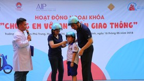 A  student is instructed how to wear helmet corectly (Photo: SGGP)