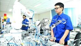 Students are monitoring robots and automatic production systems in SHTP. Photo by CAO THANG.