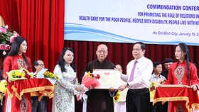 Chairman Ma and Health Minister Tien give certificates of merit to teams and individuals that well contributed to the charitable activities to take care of poor people (Photo: SGGP)