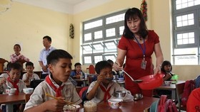 A teacher give meal portion to children (Photo: SGGP)