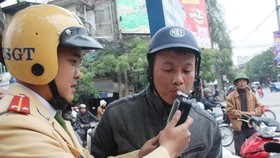 A traffic police officer takes an alcohol test for a motorcyclist. (Photo: VNA)