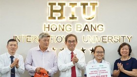 HIU President Ho Thanh Phong grants scholarship to the poor girl (Photo;l SGGP)