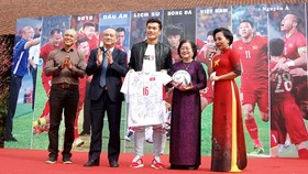 Former Vice President of Vietnam and Chairman of Vu A Dinh Scholarship Fund Truong My Hoa receives the jerseys and ball from representatives of the football team(Photo:Huy Dung)