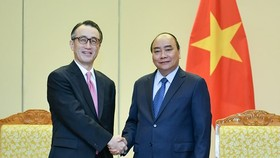 Vietnamese Prime Minister Nguyen Xuan Phuc (R) and Kanetsugu Mike, Executive President of Mitsubishi UFJ Financial Group (MUFG) Bank