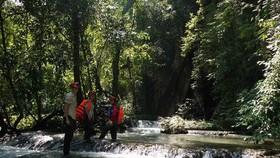 Visitors wade through a stream in Phong Nha. (Photo by Deb Limbert)