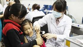 Phụ huynh đưa con đi chích ngừa tại Viện Pasteur