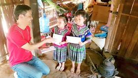 Ông Hiroshi Yokota ,Tổng giám đốc Công ty Canon Việt Nam, tặng quà học sinh nghèo xã Nà Hầu