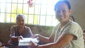 Nhà văn Trầm Hương tặng quà giúp đỡ bà Phan Thị Niết