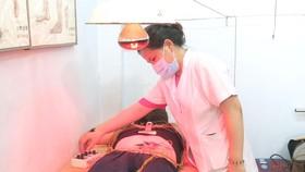 Bác sĩ của Trạm Y tế phường Tân Quý (quận Tân Phú) thăm khám cho người bệnh