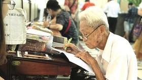 Ông Dương Văn Ngộ dịch thư tay cho khách ở Bưu điện thành phố