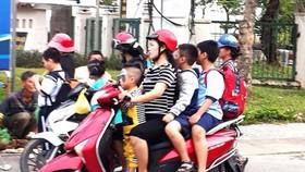 不少家長尚未注重讓孩子坐在摩托車上要戴安全帽。