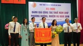 市人委會副主席陳永線(左三)向市稅務局集體頒贈政府錦旗。(圖源:阮桂)