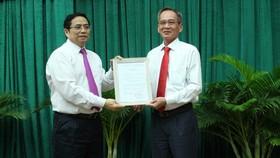 中央組織部長范明政(左)向呂文雄同志頒發出任後江省省委書記職稱批准《決定》。