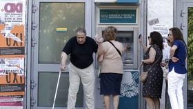 民眾在自助取款機前排隊取錢。(示意圖源:Christian Hartmann)