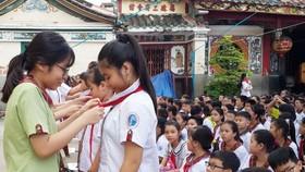 陳佩姬學校九年級學生向六年級新生轉交紅領巾。