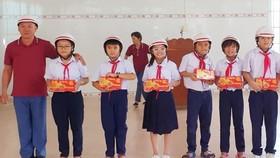 鄭成龍理事長向兒童贈送月餅及安全帽。