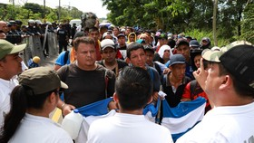 大批準備前往美國的中美洲移民目前滯留在美墨邊境,墨西哥警方(白衣者)週三在恰帕斯州展開行動,拘留非法入境的薩爾瓦多移民。(圖源:AFP)