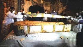 11月24日,在埃及盧克索省,工作人員在墓室內打開一口裝有木乃伊的棺材。(圖源:互聯網)