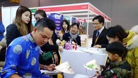 參展者觀看越南斗笠繪畫作品。