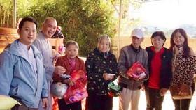 該廟慈善組組長鄒國榮(左一)與寶光浮寺的 振啟法師(左二)向少數民族同胞派發禮物。