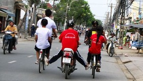 一輛摩托車推著2輛自行車在街上並排駕駛的情景要不得。