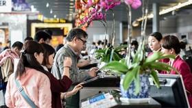 旅客在櫃台辦理登機手續。(圖源:新華社)