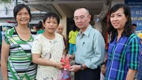 本報編委兼編輯部主任范興(右二)向患上腦腫瘤的華人病童陳雅珍贈送禮物代金。