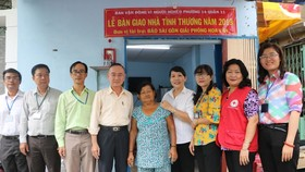 范興主任(左四)與地方領導同張南瑛(中) 在屋前留影。