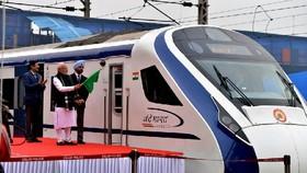 當地時間15日,在印度首都新德里,印度總理莫迪(前)在開通運營儀式上手持指揮列車的旗幟。(圖源:互聯網)