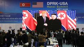 記者在國際新聞中心觀看和拍攝金正恩與特朗普會面的電視直播。(圖源:新華社)