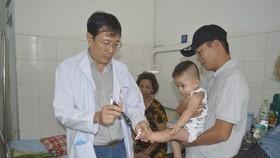 同塔省全科醫院兒童科長黃鴻福醫生在為一名病童看診。(圖源:陳玉)