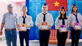 忠義華文學校董事長李鴻才(左一)向優秀生頒獎。