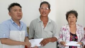 本報慈善組人員將讀者樂捐善款轉交予貧病華人。