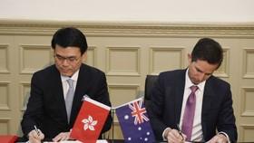 邱騰華在澳洲悉尼與澳洲貿易、旅遊和投資部長伯明翰(右)簽署香港與澳洲《自由貿易協定》和《投資協定》。(圖源:香港政府新聞網)