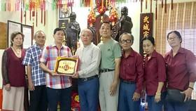 曾文良(左三)接受鄭成龍(左四)贈送紀念章。