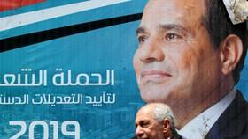 埃及開羅街頭,一名男子走過總統塞西的畫像。(圖源:路透社)