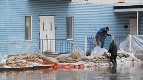 當地民眾在擺放沙袋抵禦洪水。(圖源:AFP)